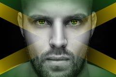 Un portrait d'un jeune homme sérieux, dans lequel les yeux est reflété le drapeau national images stock