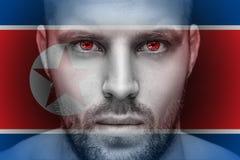 Un portrait d'un jeune homme sérieux, dans lequel les yeux est reflété le drapeau national image stock