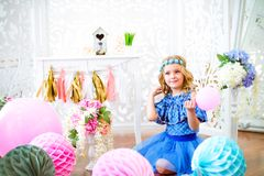 Un portrait d'une belle petite fille dans un studio a décoré beaucoup de ballons de couleur Photographie stock