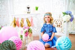 Un portrait d'une belle petite fille dans un studio a décoré beaucoup de ballons de couleur Image stock
