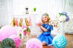 Un portrait d'une belle petite fille dans un studio a décoré beaucoup de ballons de couleur Photographie stock libre de droits