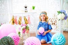 Un portrait d'une belle petite fille dans un studio a décoré beaucoup de ballons de couleur Photo stock