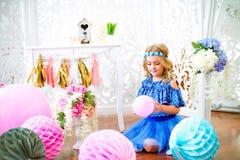 Un portrait d'une belle petite fille dans un studio a décoré beaucoup de ballons de couleur Images stock