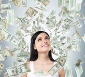 Un portrait d'une dame rêveuse dans un dessus de réservoir blanc Les notes du dollar tombent du plafond Image libre de droits