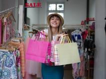 Un portrait d'une femme à la mode avec des paniers dans des ses mains dans un magasin d'habillement Concept d'achats Copiez l'esp Photographie stock