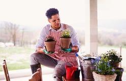 Un portrait de jardinier de jeune homme à l'intérieur à la maison, plantant des fleurs photographie stock