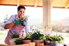 Un portrait de jardinier de jeune homme dehors à la maison, plantant des fleurs image stock