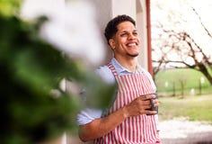 Un portrait de jardinier de jeune homme dehors à la maison, tenant une tasse de café photos libres de droits