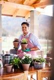 Un portrait de jardinier de jeune homme dehors ? la maison, plantant des fleurs photographie stock