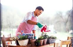 Un portrait de jardinier de jeune homme dehors ? la maison, plantant des fleurs photo libre de droits
