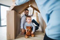 Un portrait de jeune famille avec une fille d'enfant en bas ?ge, se d?pla?ant le nouveau concept ? la maison image libre de droits