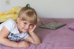 Un portrait de la petite fille caucasienne blonde mignonne s'asseyant sur un lit et souriant rêveusement La fille a grand beau gr photographie stock libre de droits