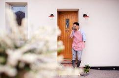 Un portrait de la position de jardinier de jeune homme devant la porte à la maison image libre de droits