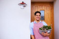 Un portrait de la position de jardinier de jeune homme devant la porte ? la maison Copiez l'espace photos stock
