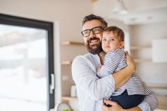 Un portrait de père avec une fille d'enfant en bas âge à l'intérieur, étreignant images stock