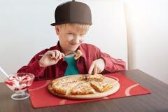 Un portrait du mâle beau d'enfant s'est habillé dans la chemise rouge élégante et le chapeau noir mangeant de la pizza et de la g Image libre de droits