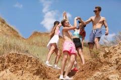 Un portrait intégral d'un groupe d'ados sur un dessus d'une colline donne à cinq sur un fond brouillé naturel Images libres de droits