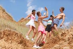 Un portrait intégral d'un groupe d'ados sur un dessus d'une colline donne à cinq sur un fond brouillé naturel Image libre de droits