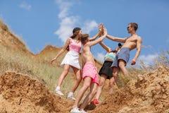 Un portrait intégral d'une société des ados sur un dessus d'une colline donne à cinq sur un fond brouillé naturel Photo libre de droits