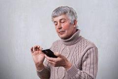 Un portrait latéral de l'homme mûr faisant habiller des rides et des cheveux gris dans le chandail tenant le smartphone dans son  Images stock