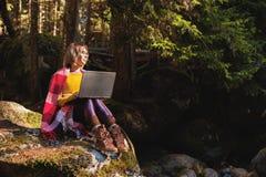 Un portrait modifié la tonalité d'une fille de sourire de hippie d'indépendant avec des verres s'est habillé dans une couverture  Photographie stock
