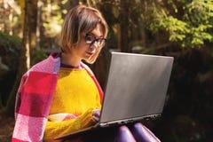 Un portrait modifié la tonalité d'une fille de sourire de hippie d'indépendant avec des verres s'est habillé dans une couverture  Photo libre de droits