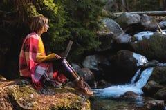 Un portrait modifié la tonalité d'une fille de sourire de hippie d'indépendant avec des verres s'est habillé dans une couverture  Image libre de droits