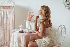 Un portrait réfléchi d'une jeune fille blonde dans une robe lumineuse i photo stock