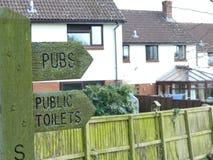 Un poste indicador en Sampford Peverell, Devon, dirigiendo hacia pubs y retretes foto de archivo libre de regalías