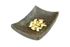 Un posto isolato degli anacardi sul piatto di legno, fondo bianco Fotografia Stock