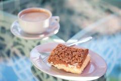 Un postre delicioso: tarta de la almendra con crema, y una taza de un caliente Imagenes de archivo