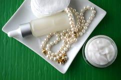 Un pot de crème de visage de beauté et de bouteille de luxe de sérum avec des perles sur le fond vert de couleur verte avec l'esp Photographie stock