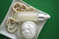 Un pot de crème de visage de beauté et de bouteille de luxe de sérum avec des perles sur le fond vert de couleur verte avec l'esp Photos stock