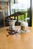 Un pot de moka et une tasse de café avec les grains de café rôtis Image libre de droits