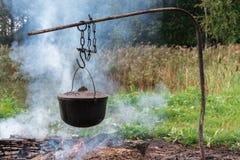 Un pot de nourriture accroche au-dessus d'un feu brûlant images libres de droits