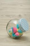 Un pot en verre avec un couvercle bleu de point de polka à moitié plein avec la sucrerie Photo stock