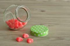 Un pot en verre avec un couvercle vert de point de polka à moitié plein avec la sucrerie Image libre de droits