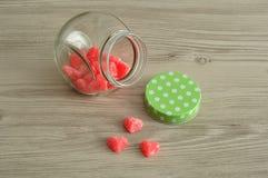 Un pot en verre avec un couvercle vert de point de polka à moitié plein avec la sucrerie Photo libre de droits