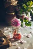 Un pot en verre avec une confiture délicieuse de rose de gourmet sur les pétales et le fond de roses dans la belle lumière Images stock
