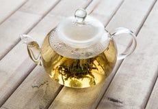 Un pot en verre de thé avec le thé chinois de fleur sur le fond en bois Photos stock
