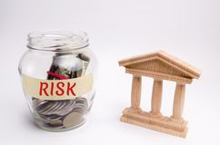 Un pot en verre et le risque d'inscription se tient à côté d'une construction d'état Le concept du risque financier et économique photographie stock libre de droits