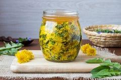 Un pot en verre a rempli de fleurs et de miel de pissenlit photos libres de droits