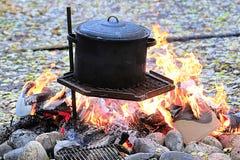 Un pot noir sur un gril au-dessus d'un grand feu photo stock
