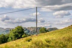 Un poteau en bois de téléphone avec dessus un côté de colline photo libre de droits
