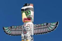 Un poteau en bois de totem à l'arrière-plan nuageux bleu Images stock