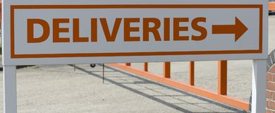 Un poteau indicateur des livraisons montrant le chemin image libre de droits