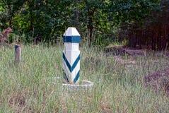 Un poteau rayé en bois dans la forêt aux carrefours dans l'herbe Photographie stock libre de droits