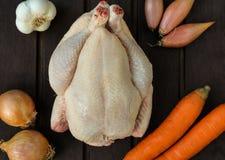 Un poulet entier avec des légumineuses sur le fond en bois Photographie stock