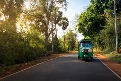 Un pousse-pousse vert de tuktuk bourdonne par des ruelles de pays autour d'Anu Image stock