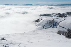 Un pré sur le dessus d'une montagne entourée par le brouillard un jour ensoleillé image libre de droits